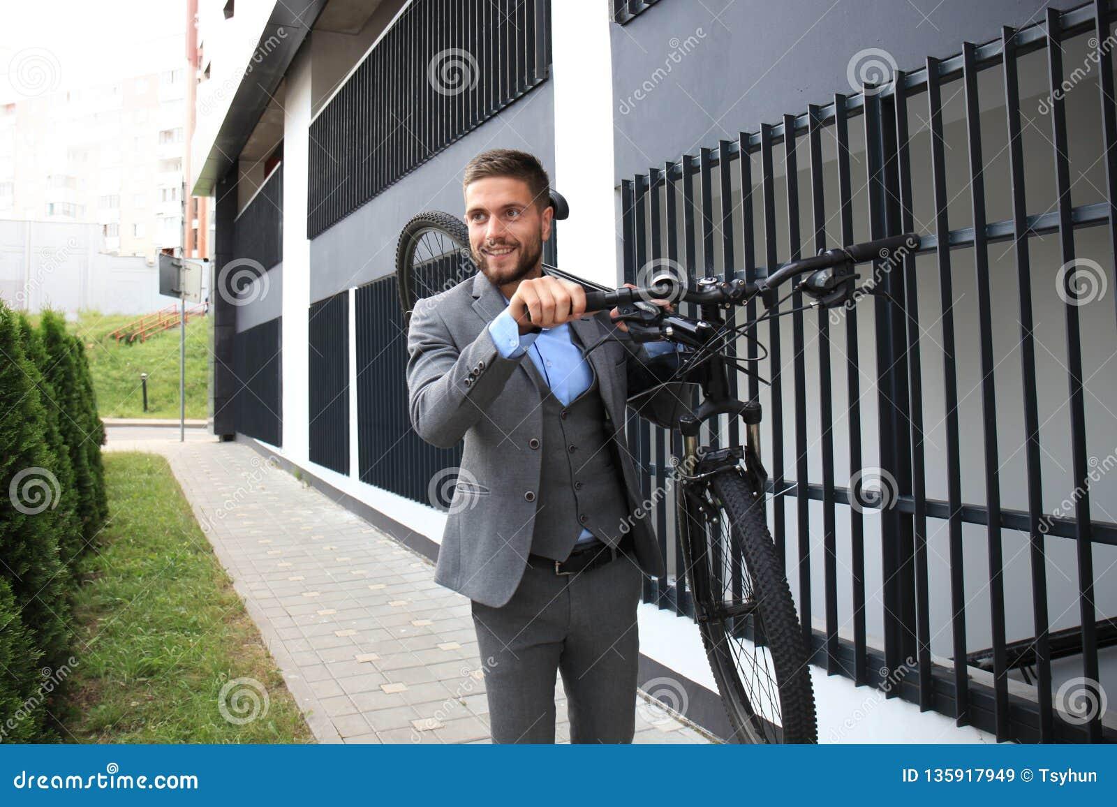 Homem de negócios novo seguro que leva sua bicicleta ao andar fora