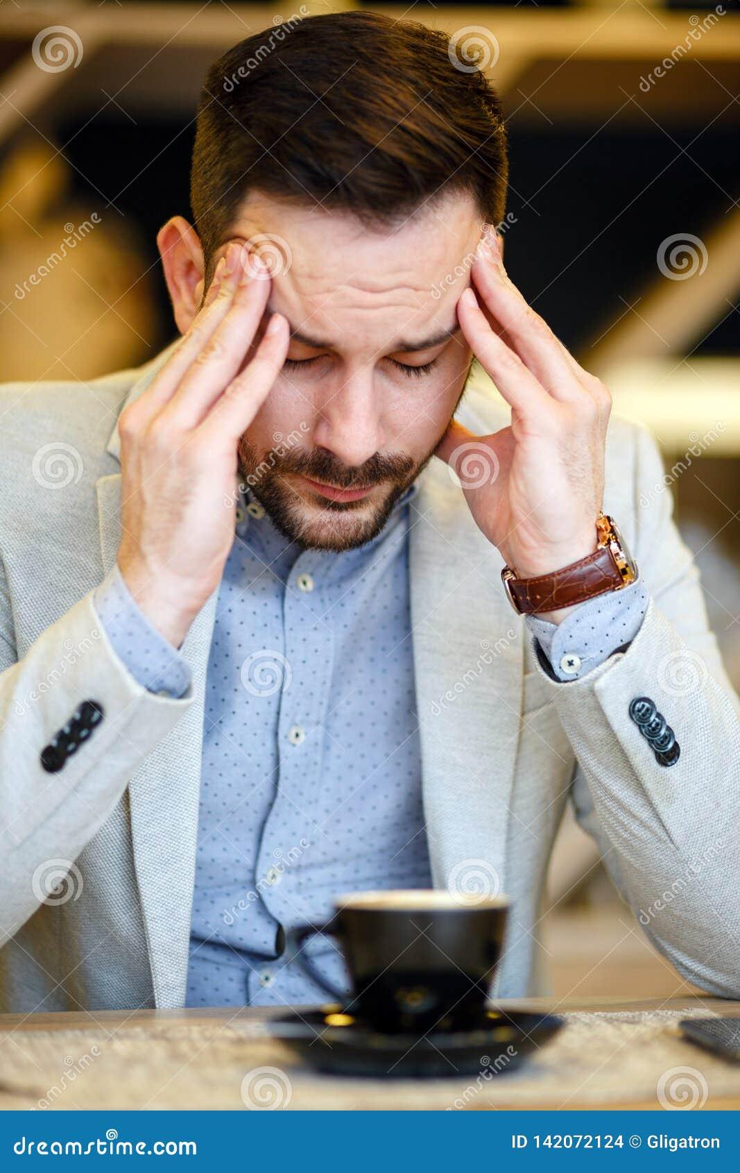 Homem de negócios novo sobrecarregado que tem uma dor de cabeça e que concentra-se ao beber uma xícara de café