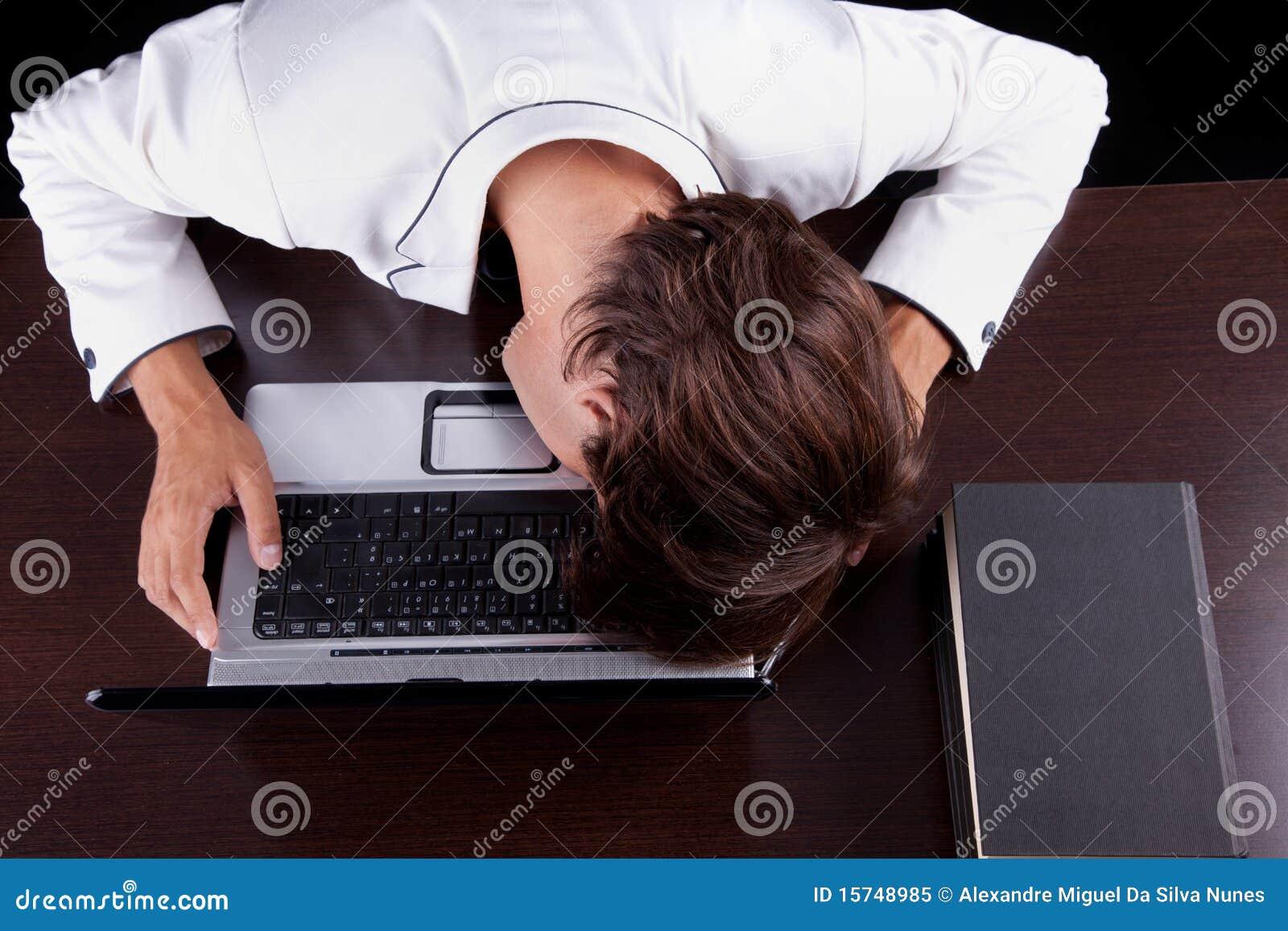Homem de negócios novo Tired com cabeça no computador