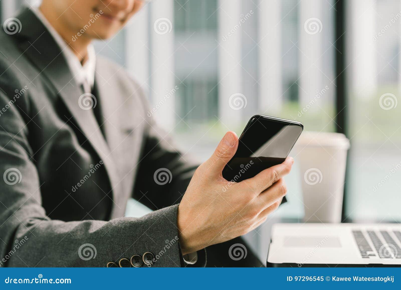 Homem de negócios ou empresário asiático que usa o smartphone e o portátil, trabalhando no escritório moderno Conceito de uma com
