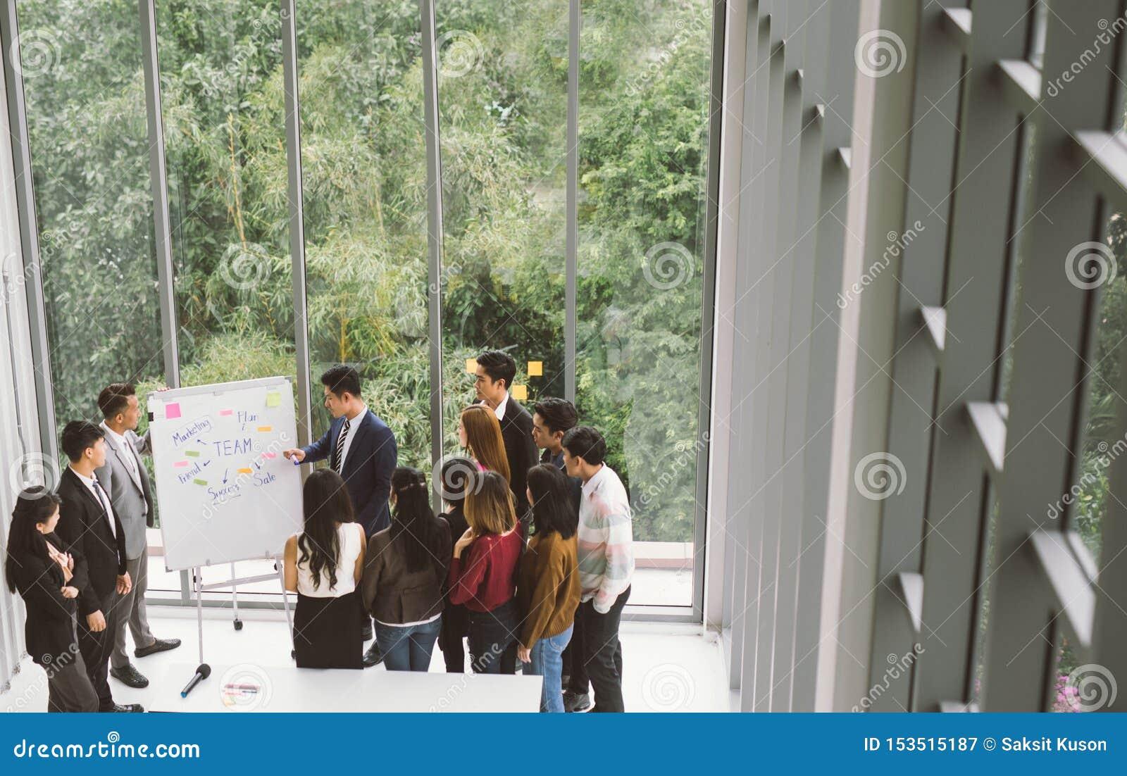 Homem de negócios que apresenta no grupo do whiteboard de executivos que estão em torno da placa branca durante o encontro no esc