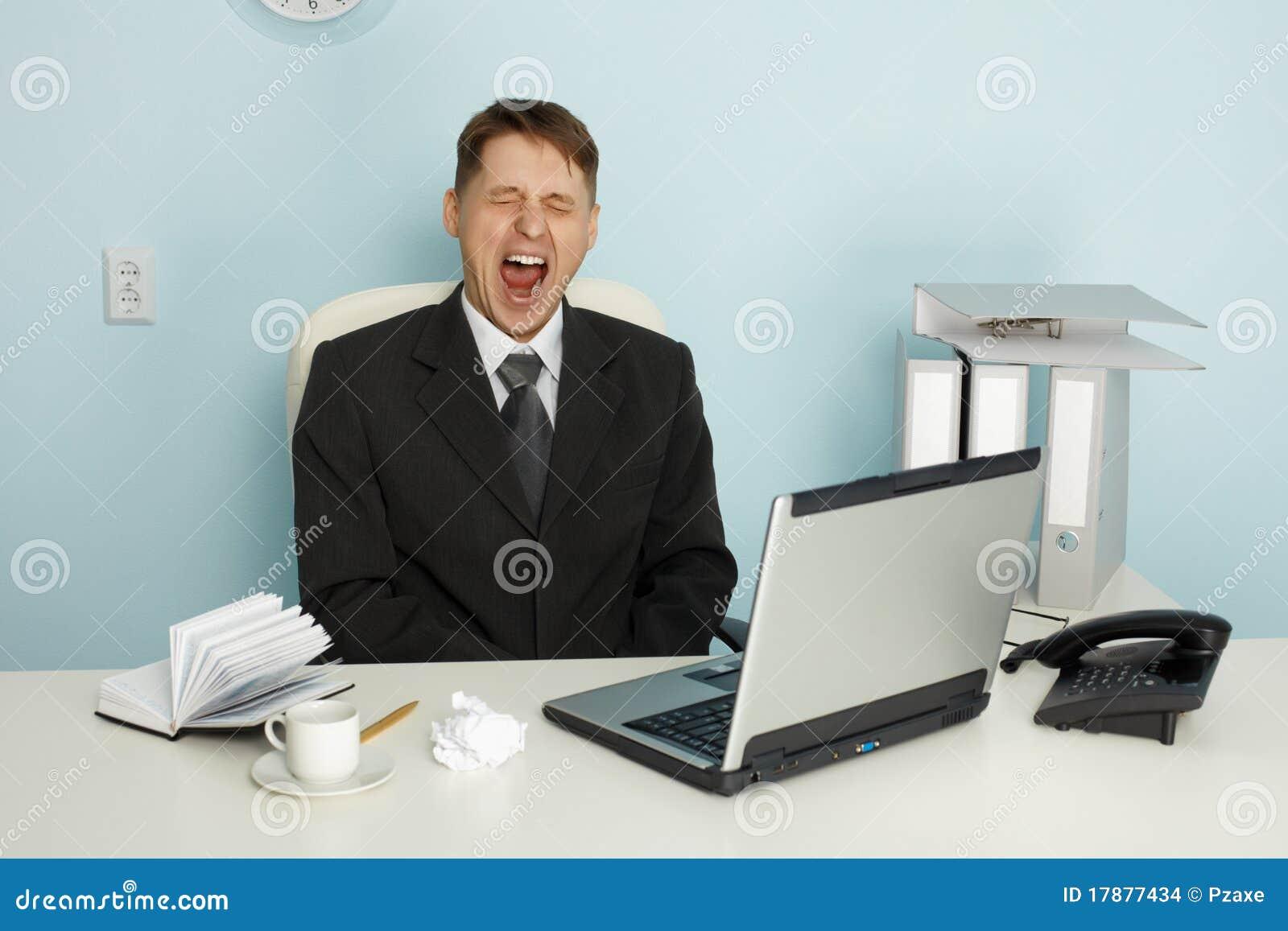 Homem de negócios que boceja do enfado e da ociosidade