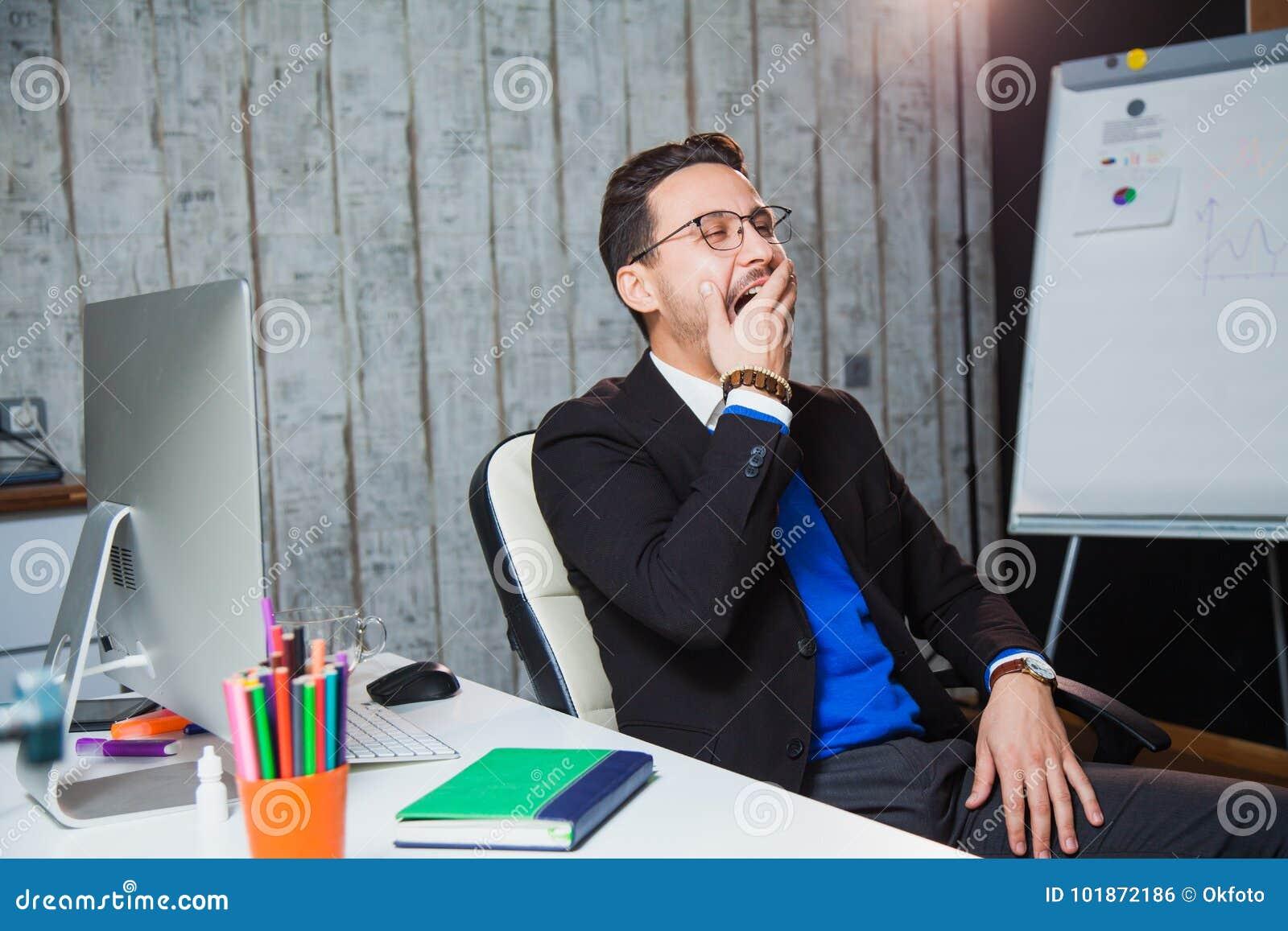 Homem de negócios que boceja em conceito de trabalho aborrecido do escritório