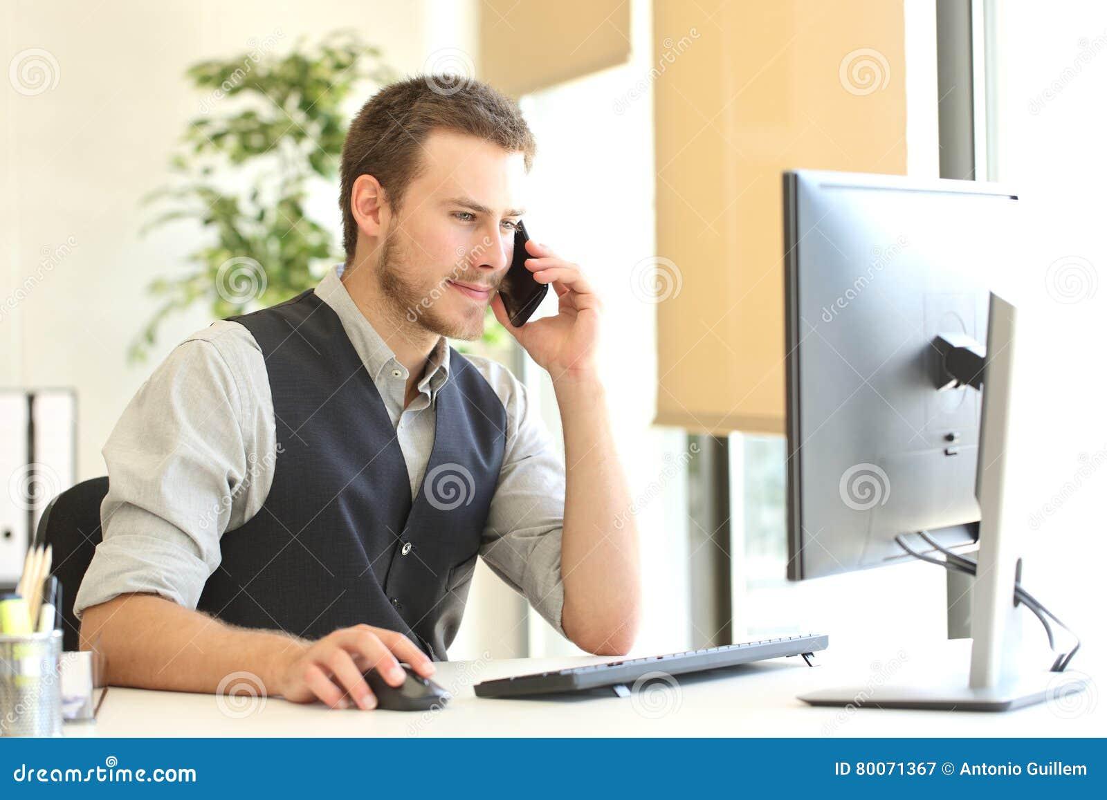 Homem de negócios que chama o telefone e que usa um computador