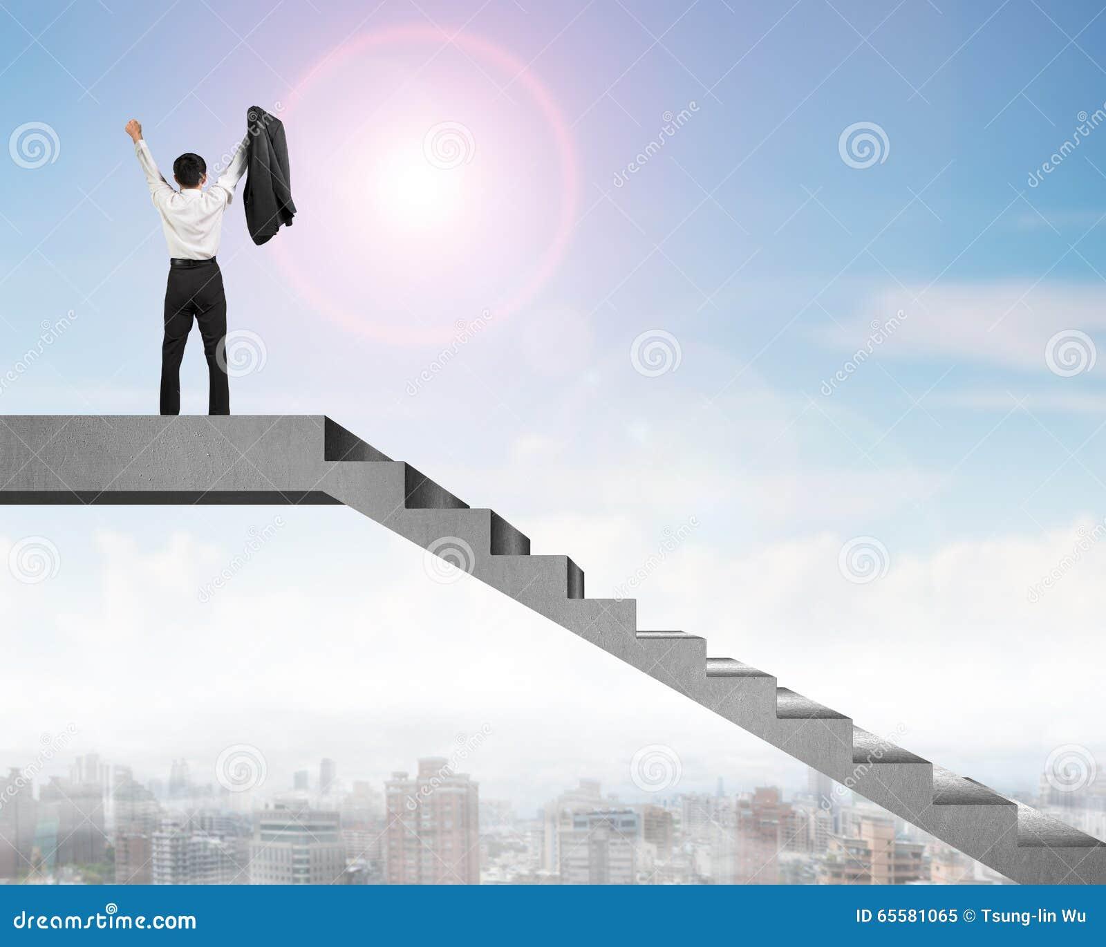 Homem de negócios que cheering sobre escadas concretas com opinião da cidade