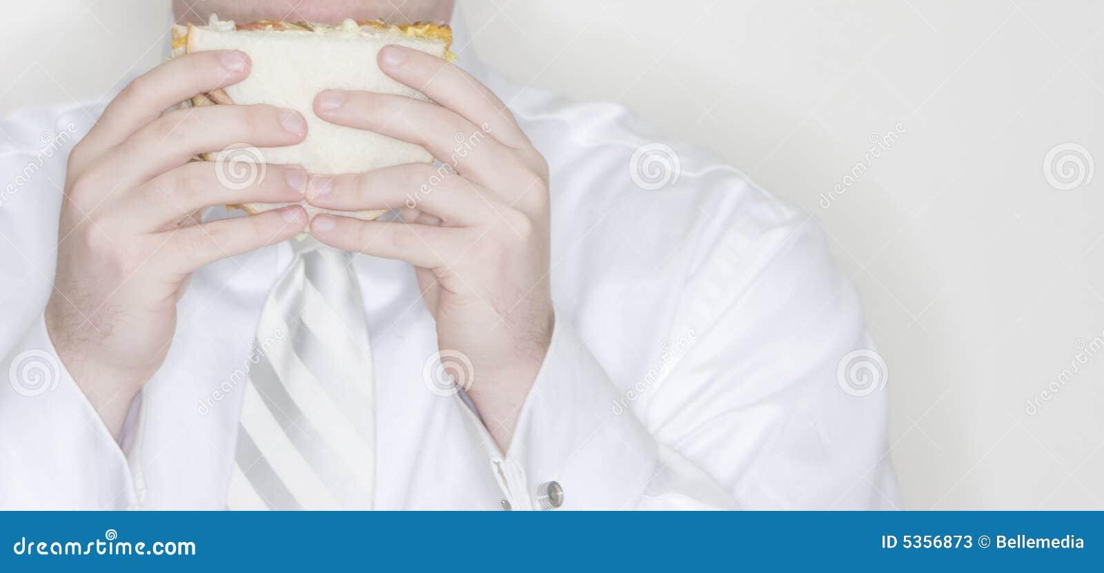 Homem de negócios que come o sanduíche