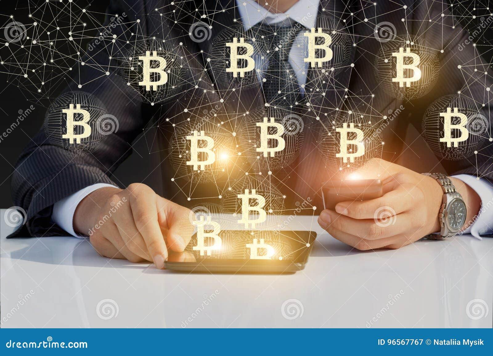 Homem de negócios que corre com bitcoin em seus telefone e tabuleta