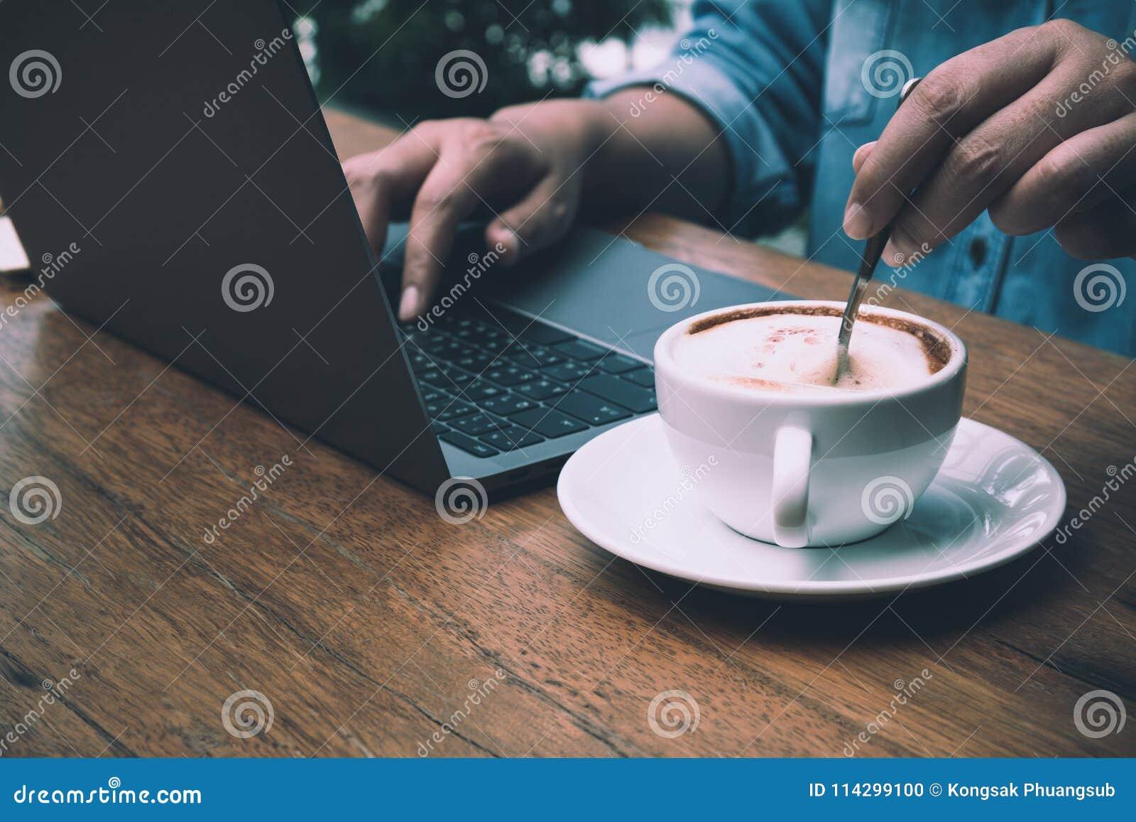 Homem de negócios que datilografa os dados no portátil para o sumário ao agitar o café