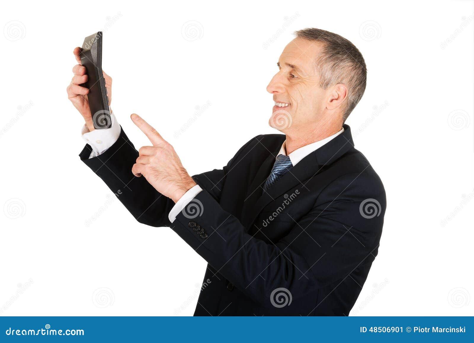 Homem de negócios que empurra o botão na calculadora