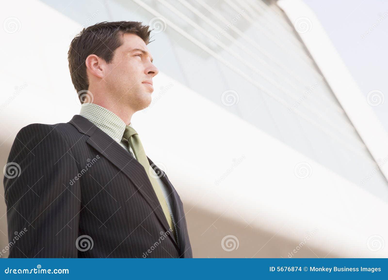 Homem de negócios que está ao ar livre pelo edifício