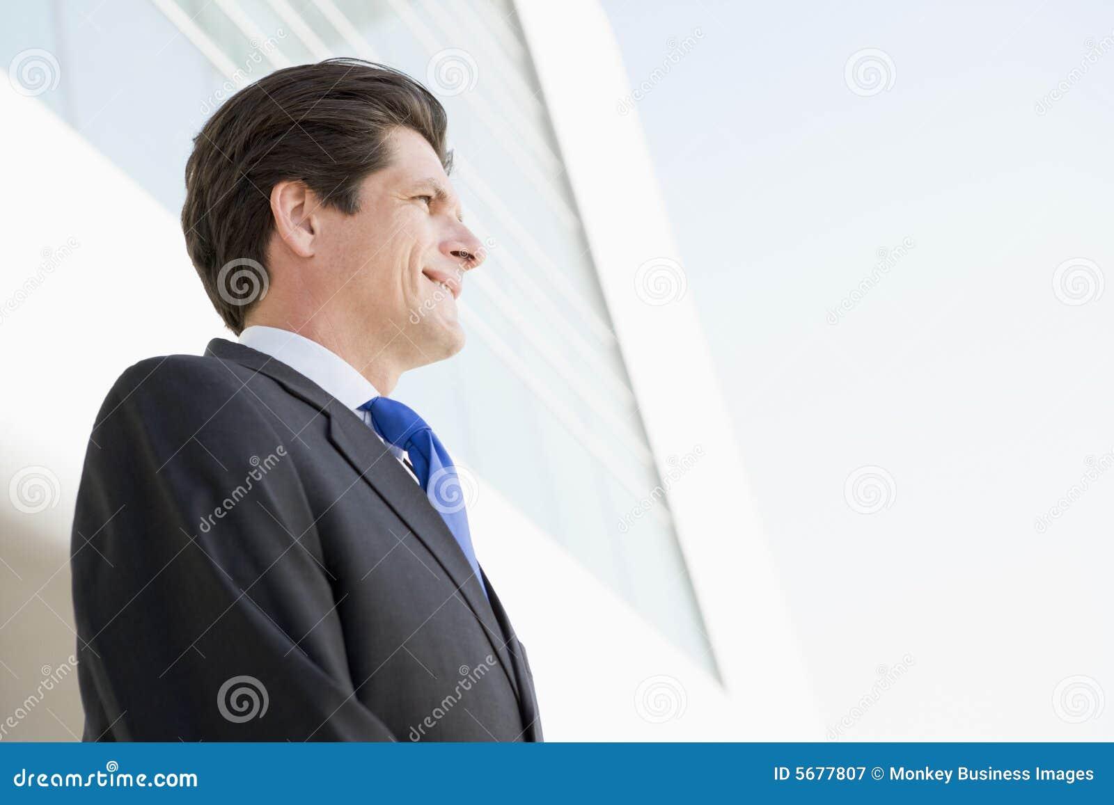 Homem de negócios que está ao ar livre pelo sorriso de construção