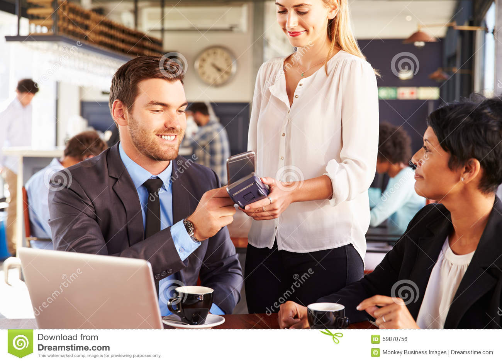 Homem de negócios que faz o pagamento pelo telefone em um café