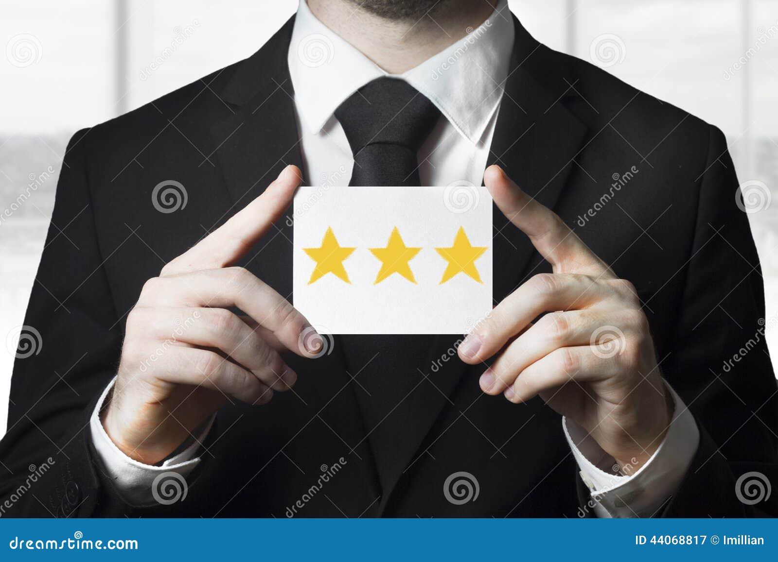Homem de negócios que guarda estrelas douradas da avaliação do sinal três