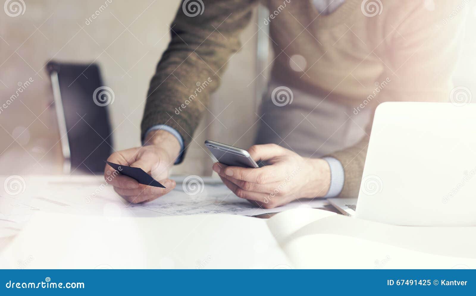Homem de negócios que guarda o businesscard da mão e que faz o smartphone da foto Projeto arquitetónico na tabela modelo horizont