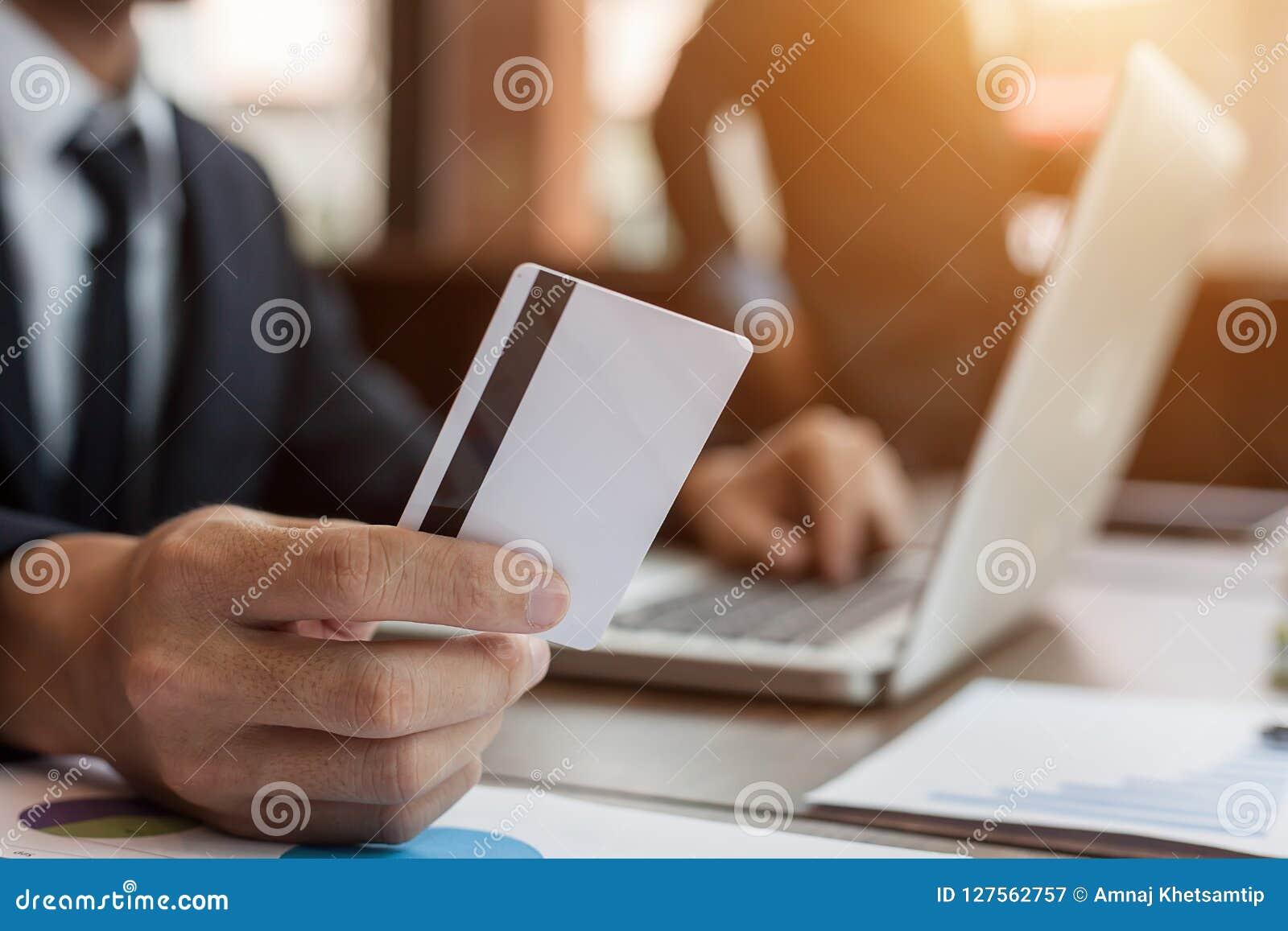 Homem de negócios que guarda o cartão de crédito e que usa o laptop