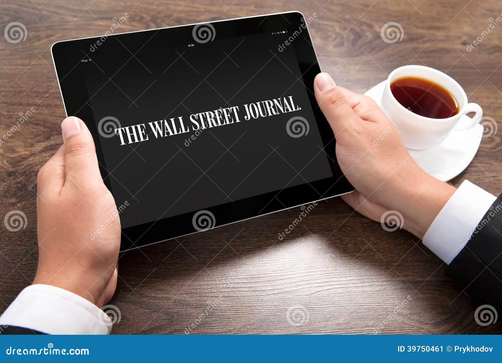 Homem de negócios que guarda o ipad com Wall Street Journal na tela