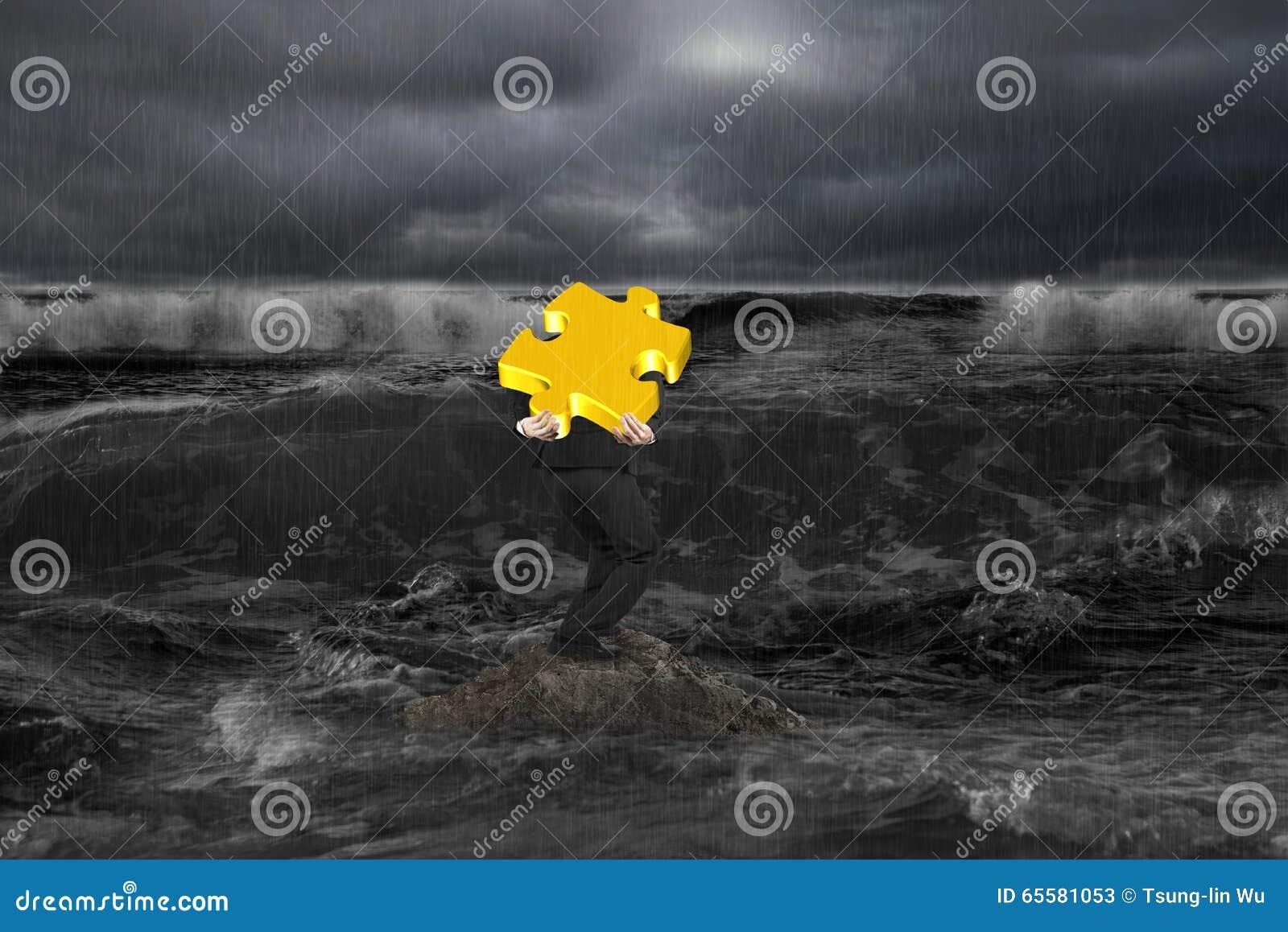 Homem de negócios que leva o enigma do ouro 3D na rocha no oceano escuro
