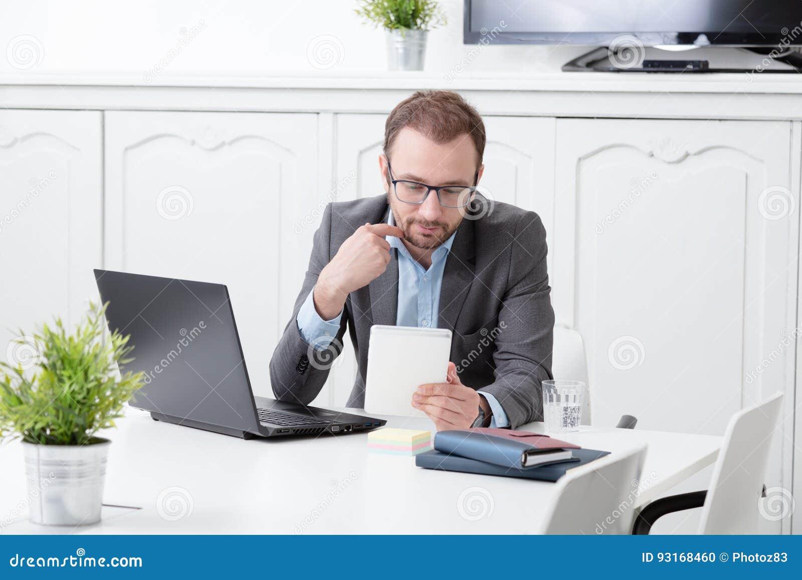 Homem de negócios que olha o dispositivo digital da tabuleta na mesa de escritório