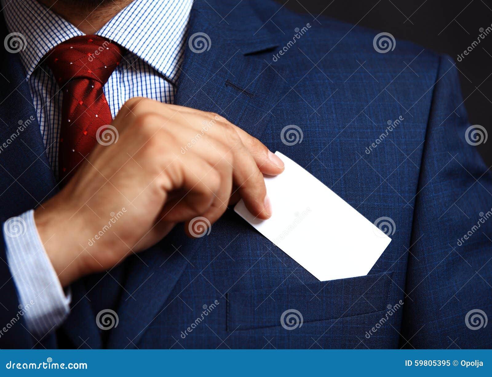 Homem de negócios que põe o cartão da visita no bolso