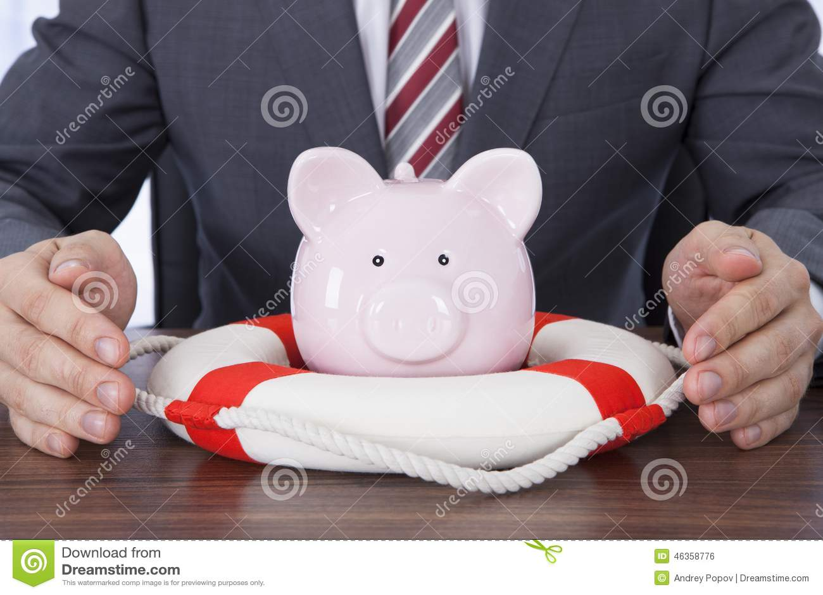 Homem de negócios que protege o piggybank com o cinto de salvação na mesa