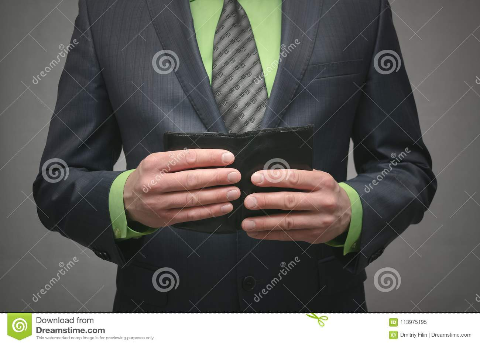 Homem de negócios que realiza nas mãos uma carteira de couro preta, fim acima da foto