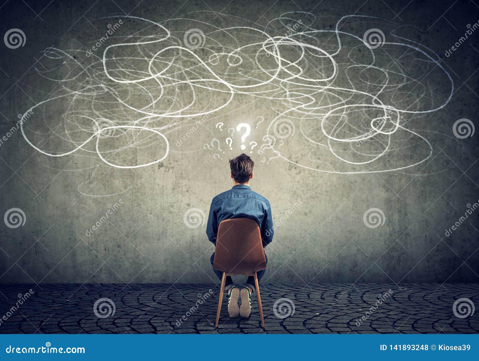 Homem de negócios que senta-se na cadeira que olha um garrancho em um sentimento da parede confuso
