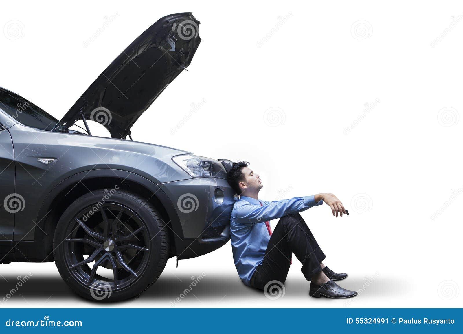 Homem de negócios que senta-se perto do carro quebrado