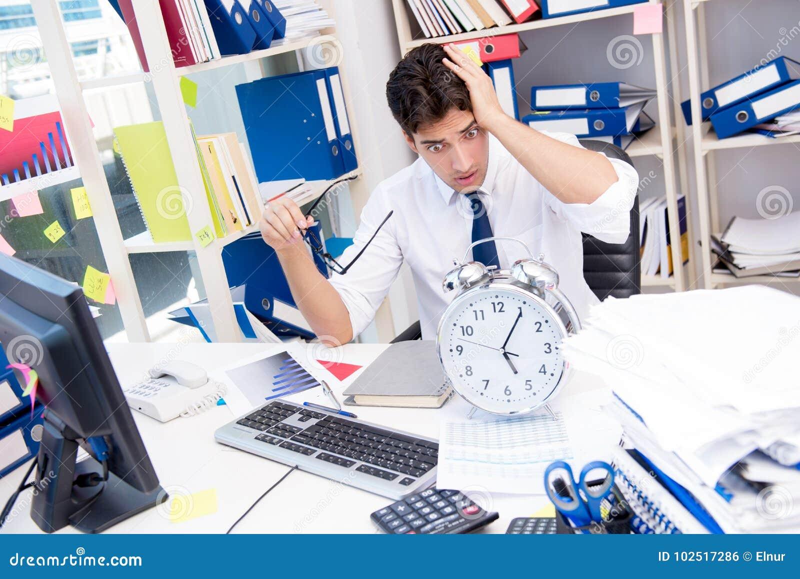Homem de negócios que trabalha no escritório com as pilhas dos livros e dos papéis