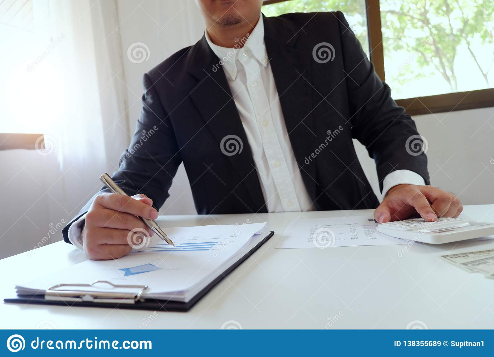 Homem de negócios que trabalha no escritório usando a calculadora com documento na mesa