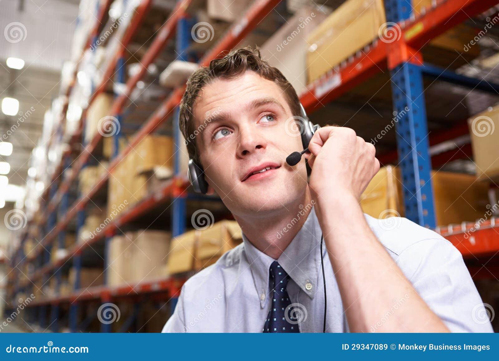 Homem de negócios que usa auriculares no armazém de distribuição