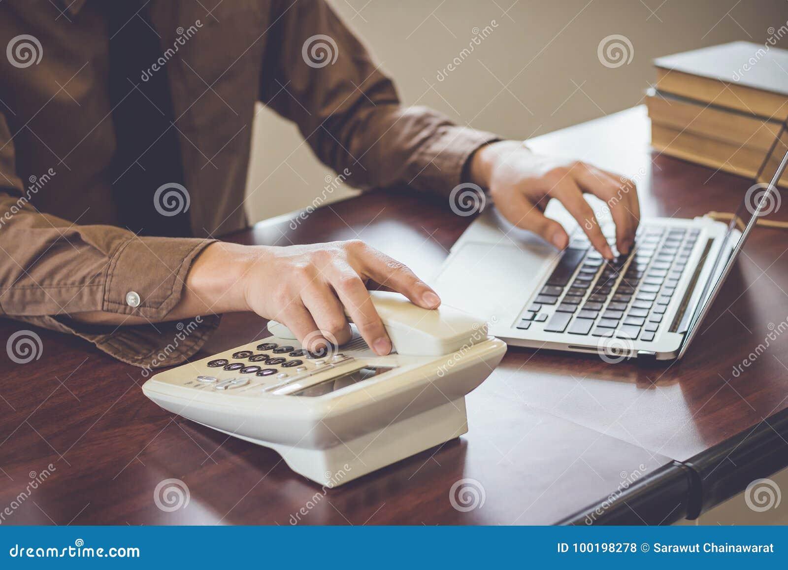 Homem de negócios que usa o cliente do contato de telefone no tom do vintage do escritório