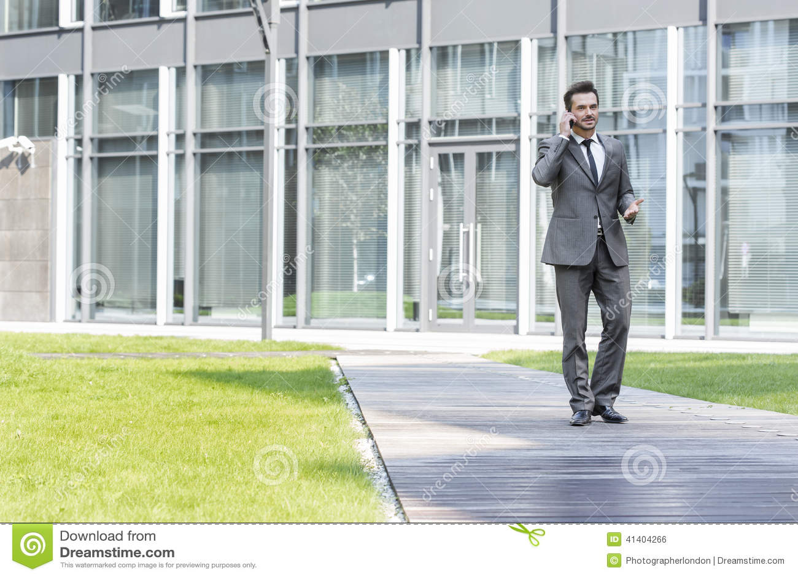 Homem de negócios que usa o telefone celular ao andar no trajeto fora do escritório