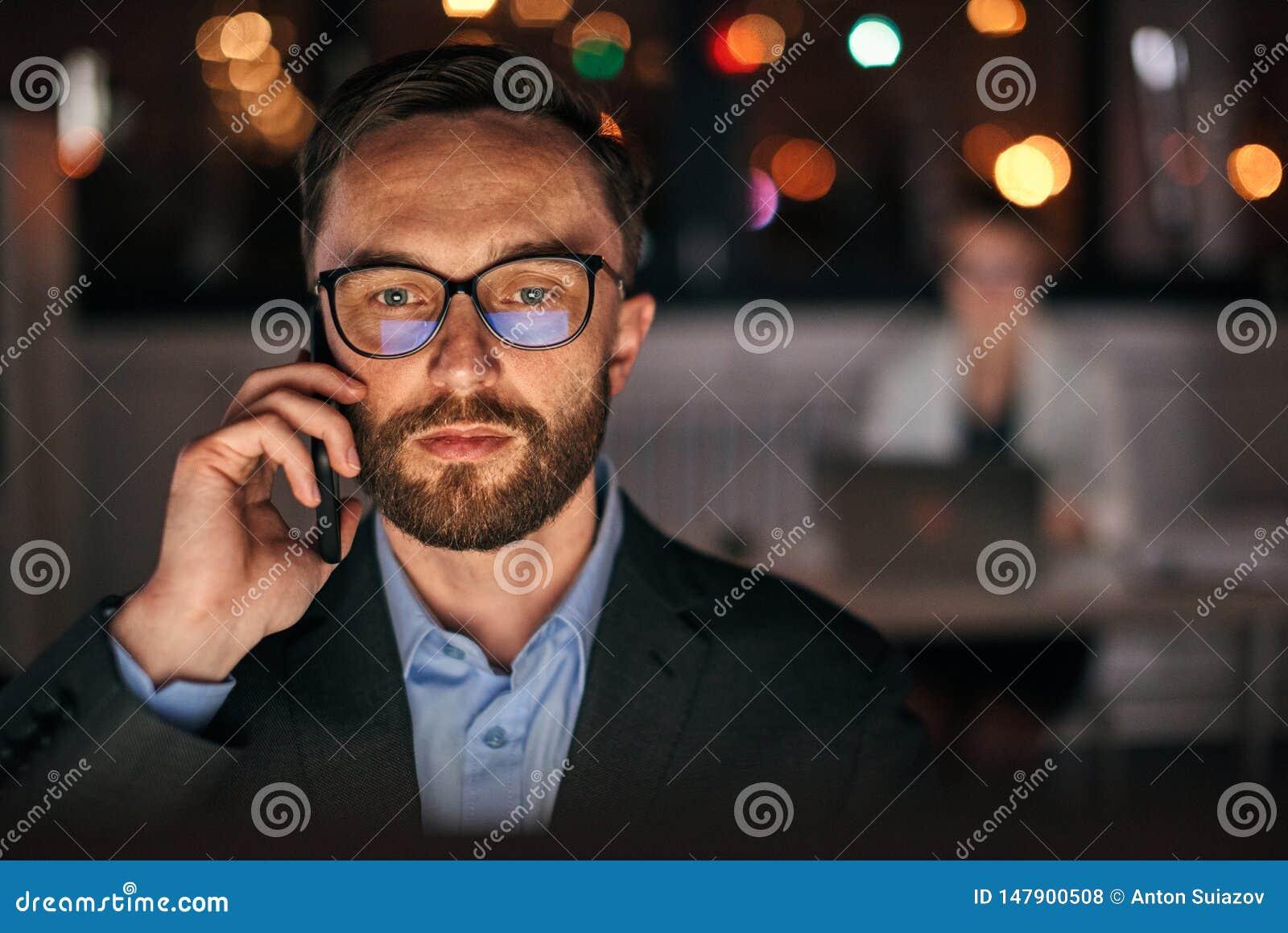 Homem de negócios que usa o telefone tardio