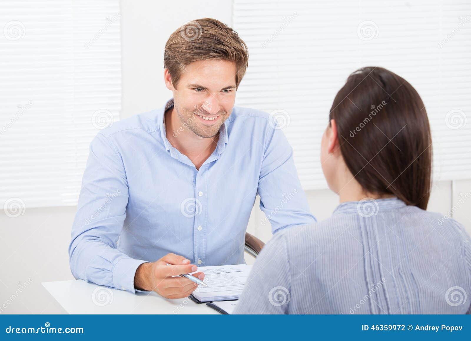 Homem de negócios que verifica o resumo do candidato fêmea durante a reunião