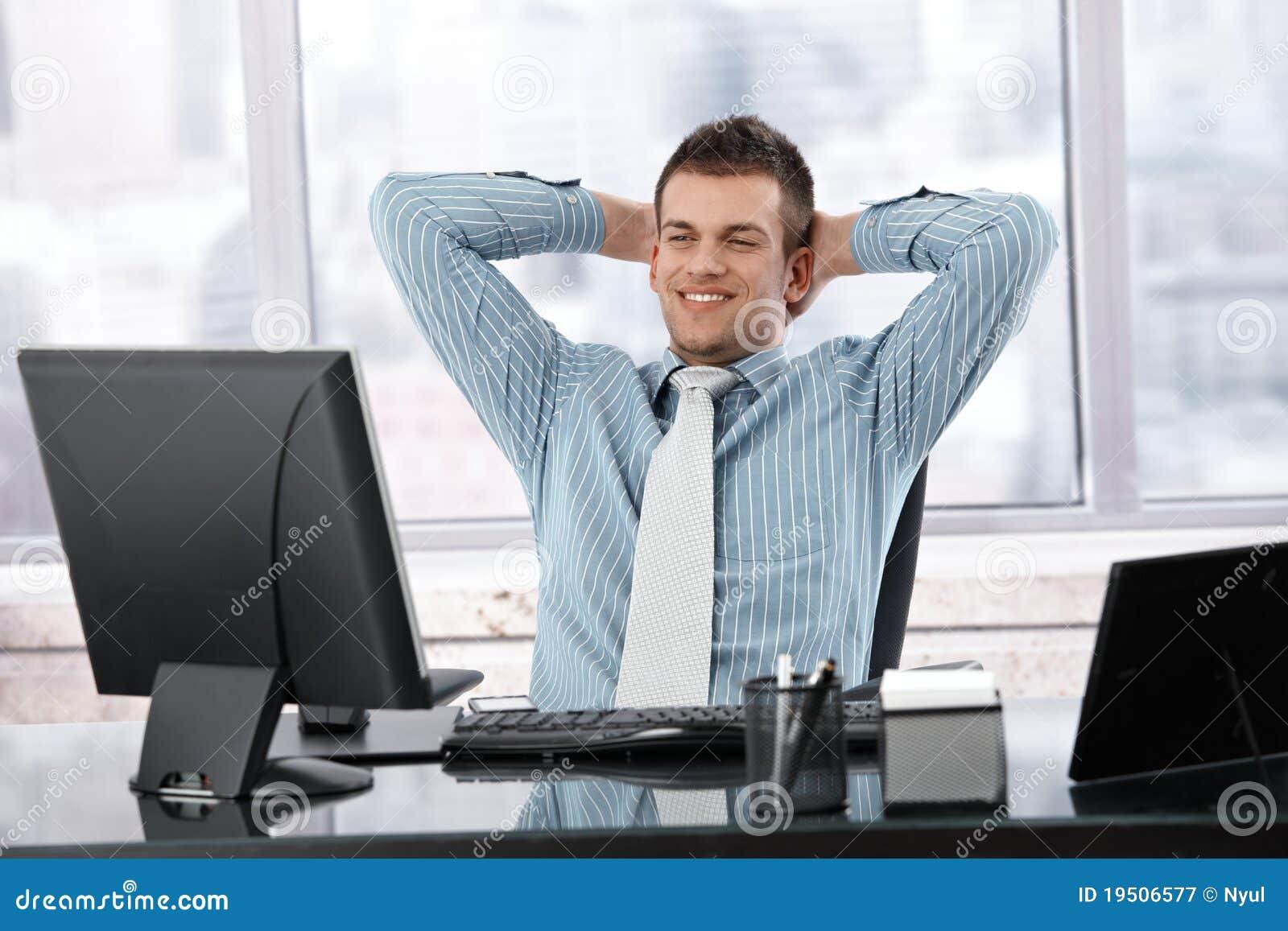 Homem de negócios satisfeito que sorri na mesa