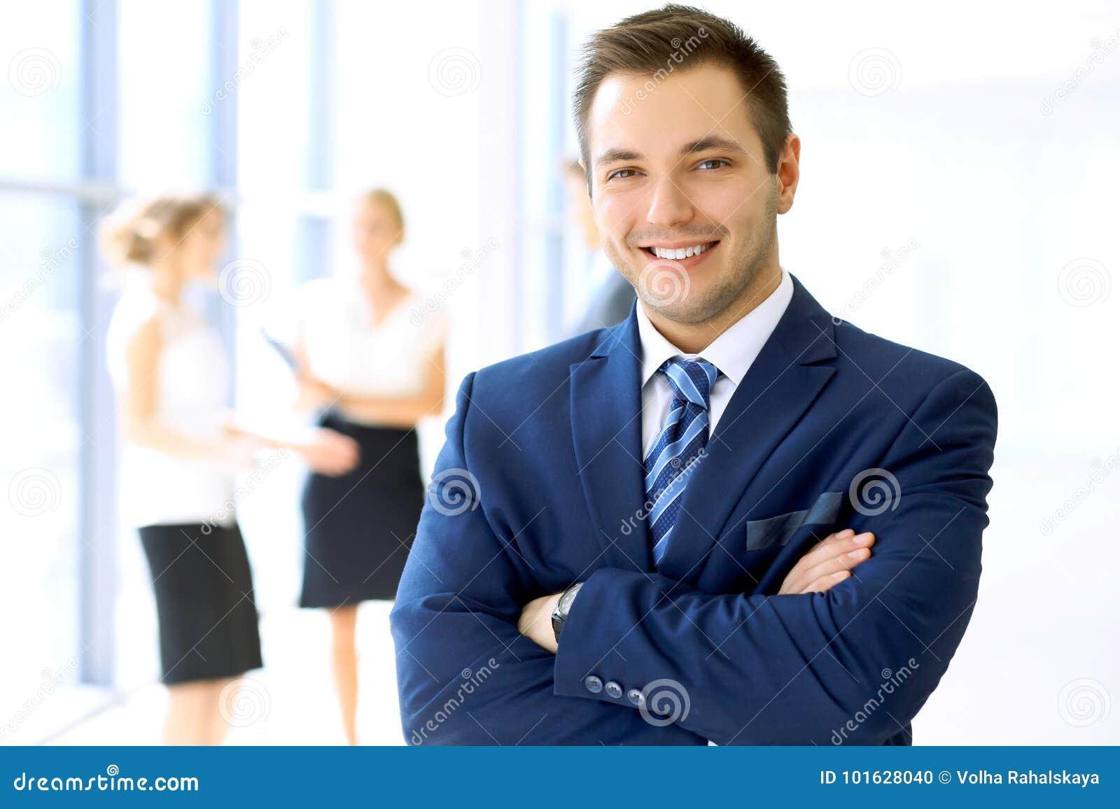 Homem de negócios de sorriso no escritório com os colegas no fundo