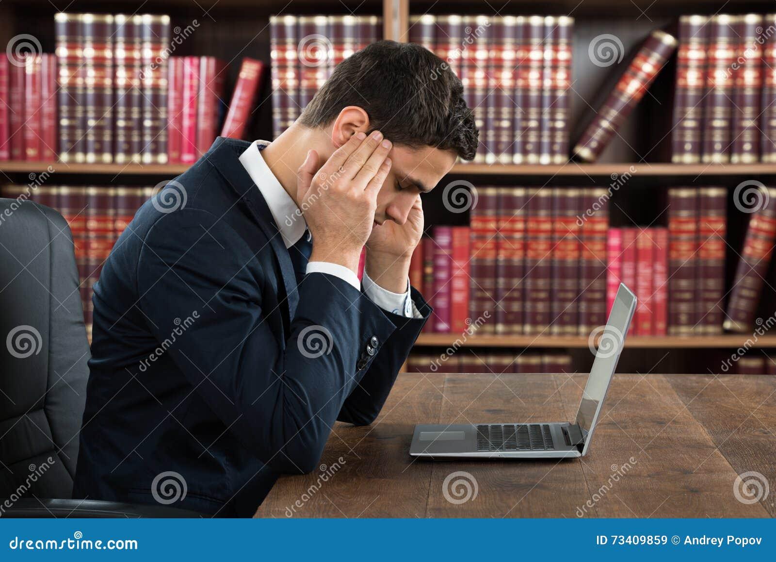 Homem de negócios Suffering From Headache ao usar o portátil