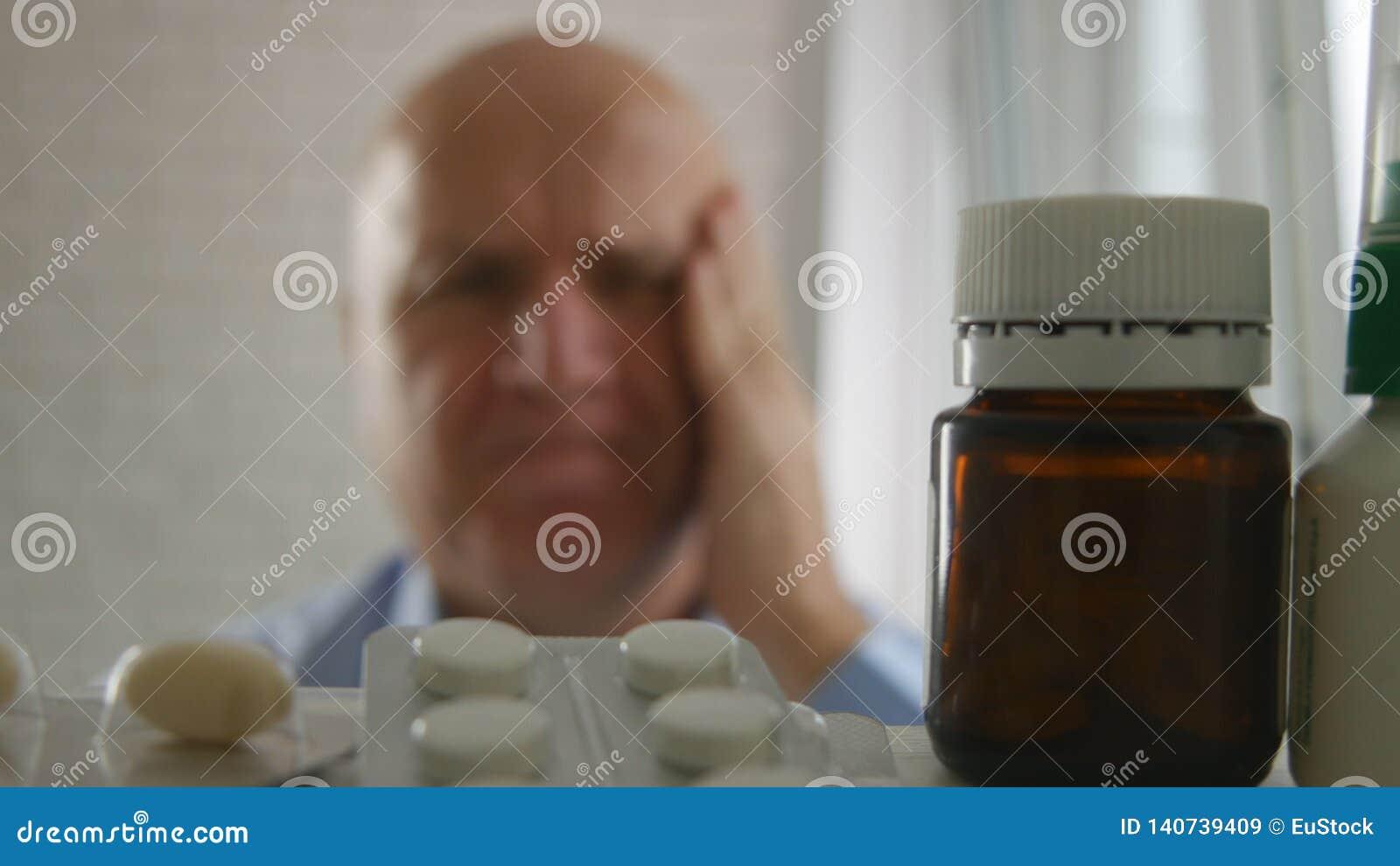 Homem de negócios Suffering um olhar grande da enxaqueca no armário de medicina para comprimidos