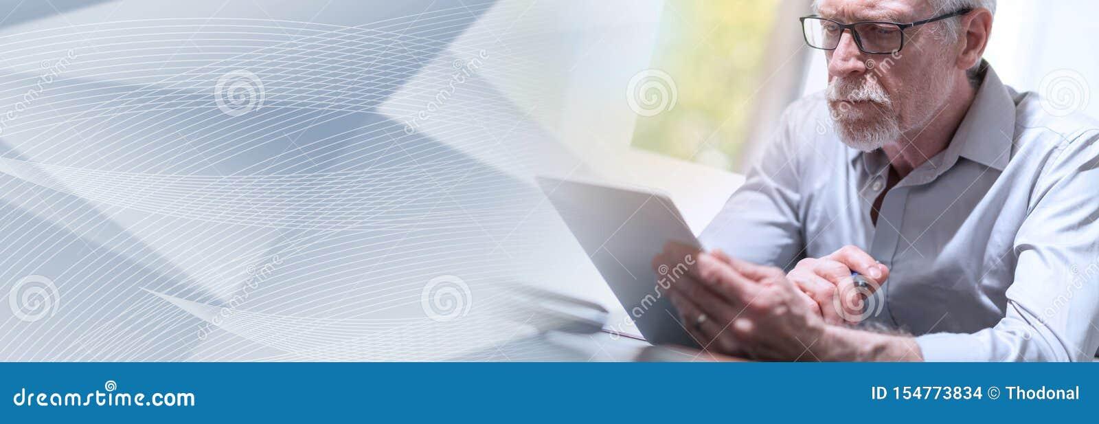 Homem de negócios superior que usa uma tabuleta digital, efeito da luz; bandeira panorâmico