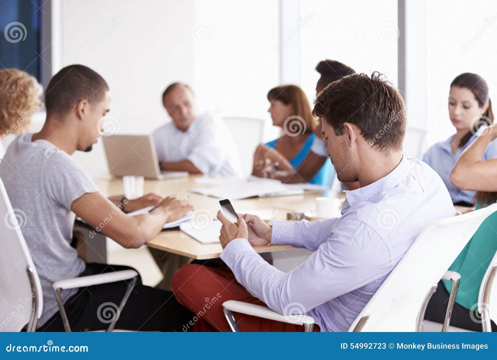 Homem de negócios Using Mobile Phone na reunião da sala de reuniões