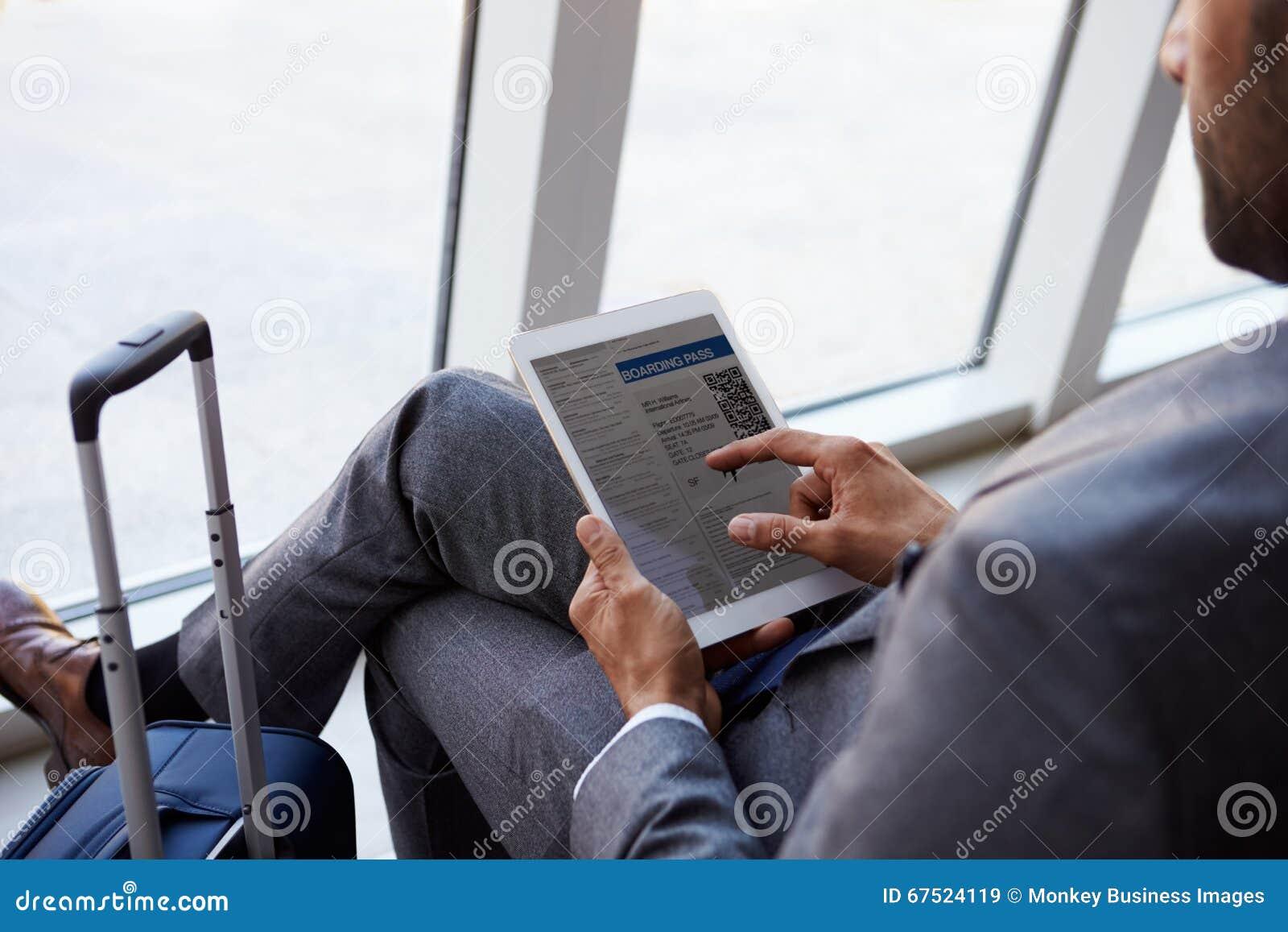Homem de negócios Viewing Boarding Pass na sala de estar do aeroporto