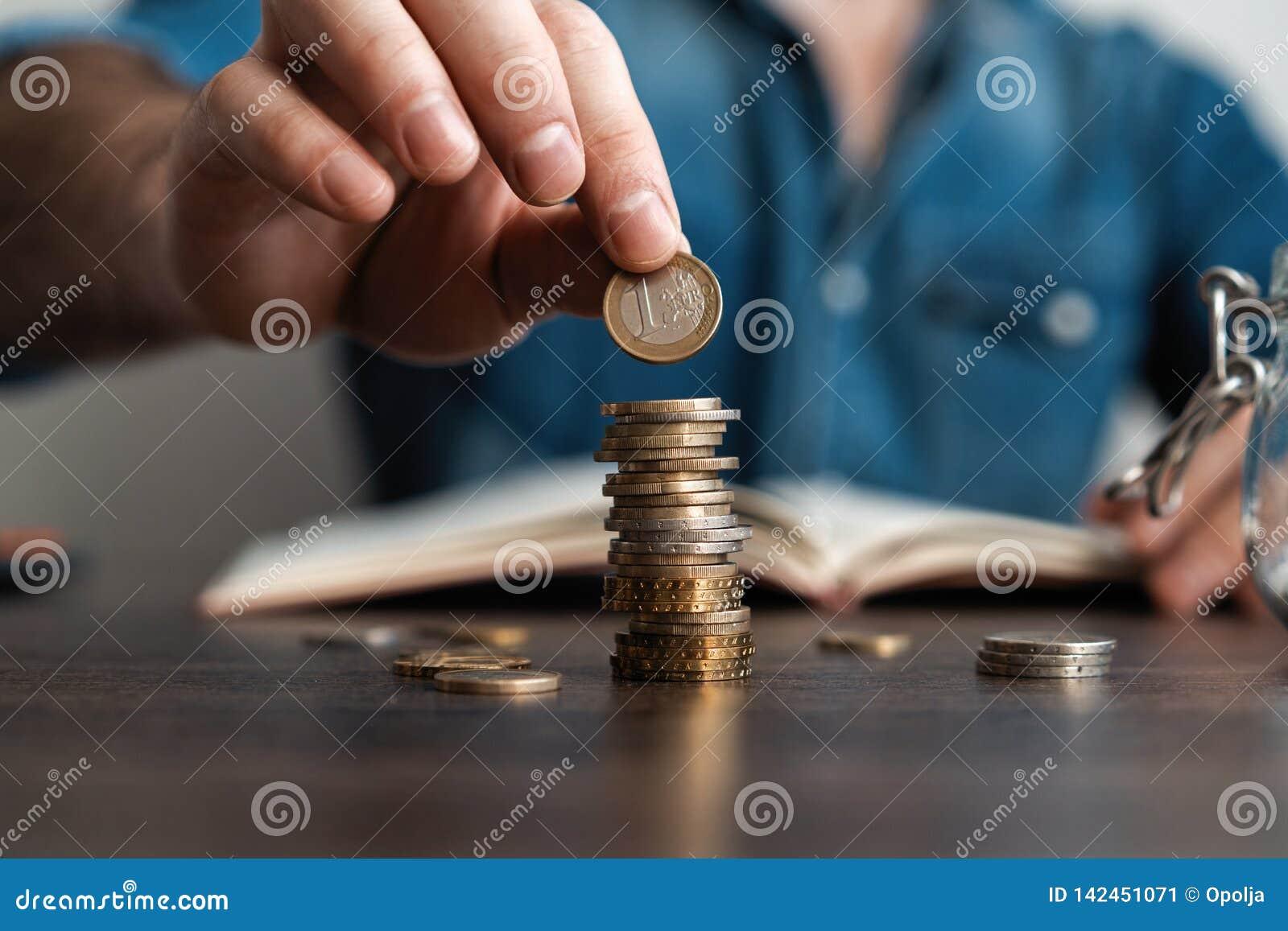 Homem de neg?cio que p?e uma moeda sobre o banco de economia da pilha das moedas e para esclarecer seu dinheiro todo no conceito