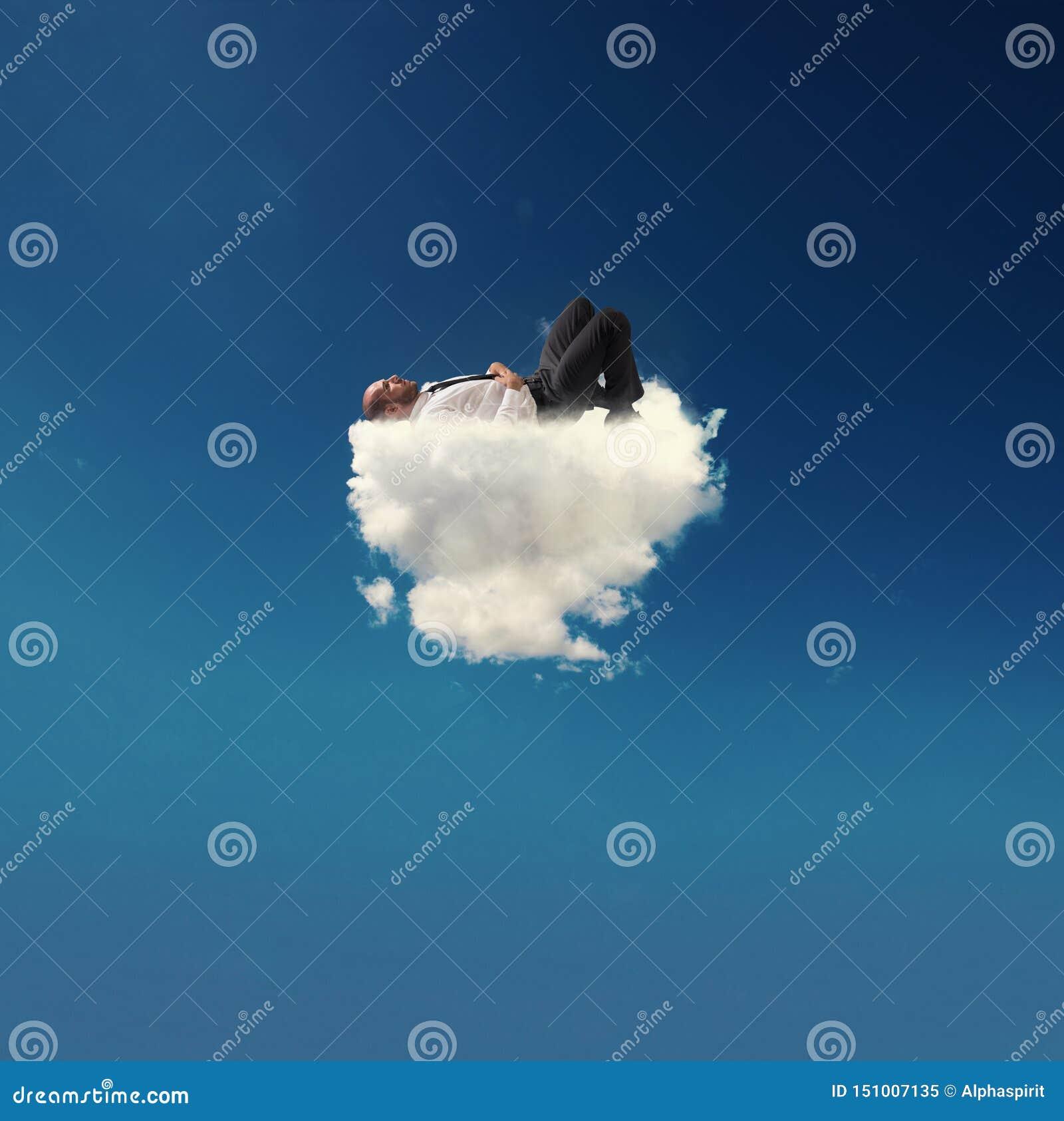 Homem de neg?cios for?ado que relaxa em uma nuvem macia