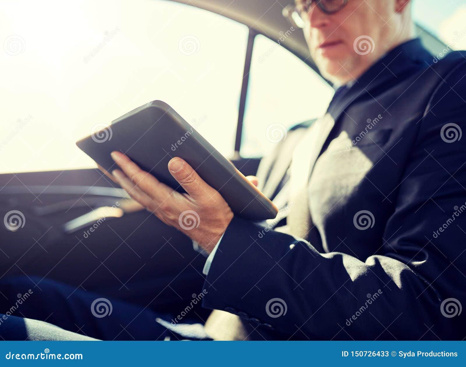 Homem de neg?cios superior com o PC da tabuleta que conduz no carro