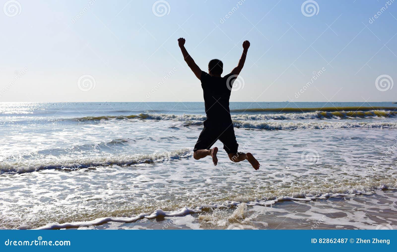 Homem de salto acima da água do mar e ondas no dia ensolarado