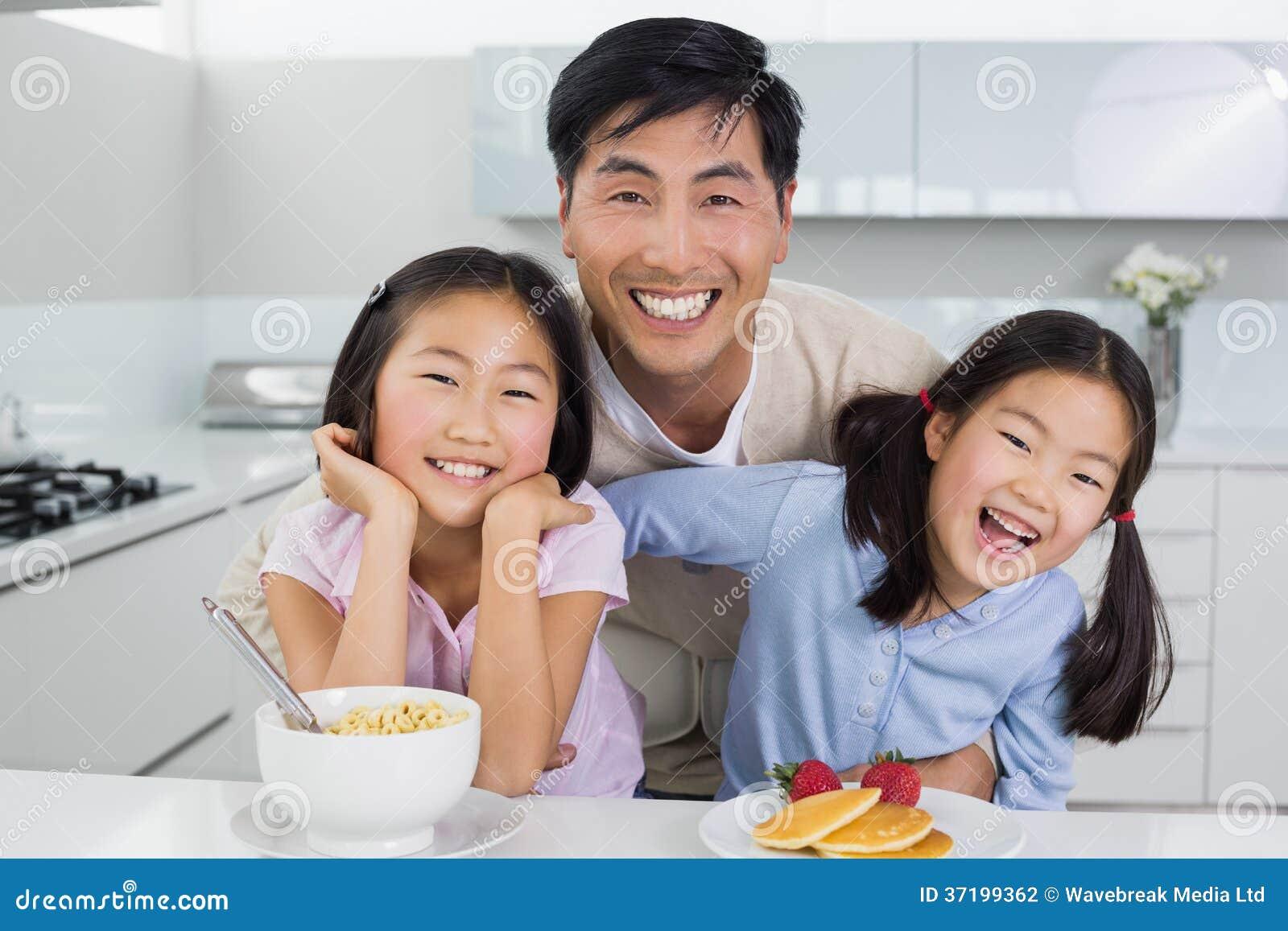 Homem de sorriso com as filhas felizes que comem o café da manhã na cozinha