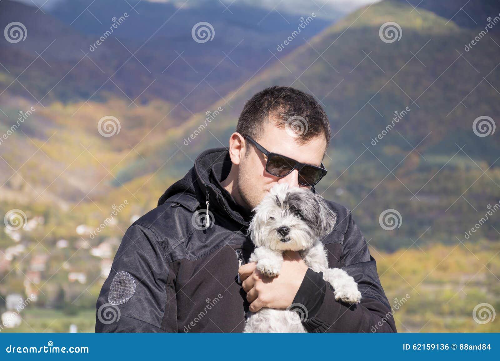 Homem de sorriso novo que abraça seu cão branco pequeno na montanha do outono