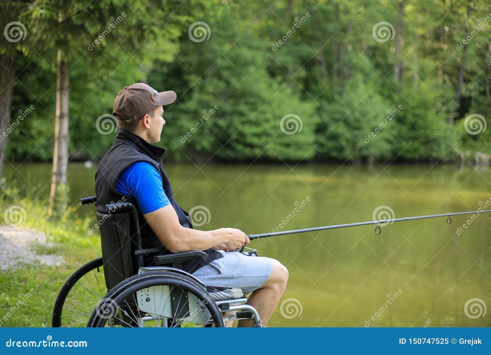 Homem deficiente na pesca da cadeira de rodas no lago