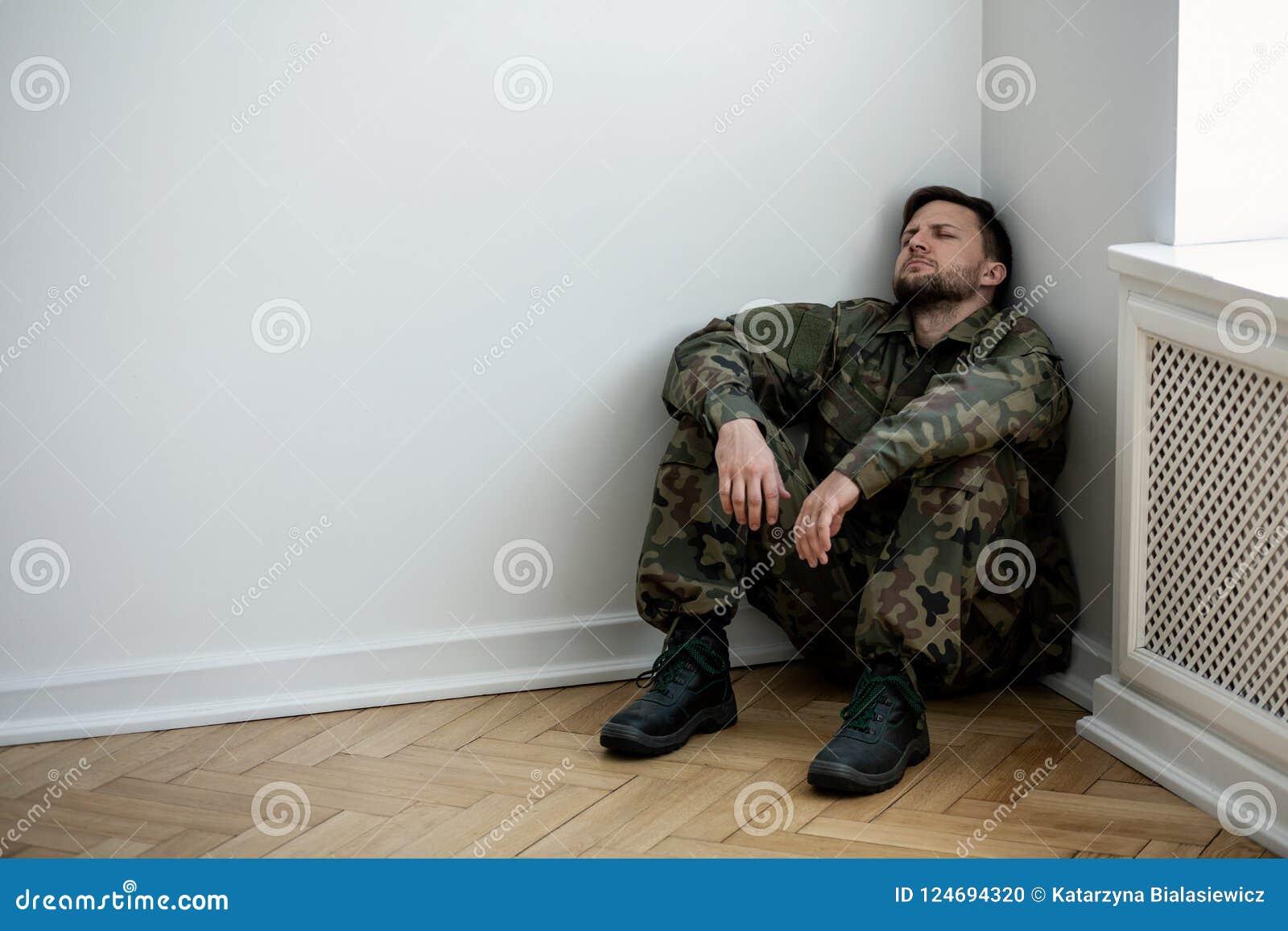 Homem deprimido do exército no uniforme que senta-se em um canto de uma sala vazia Lugar para seu cartaz na parede
