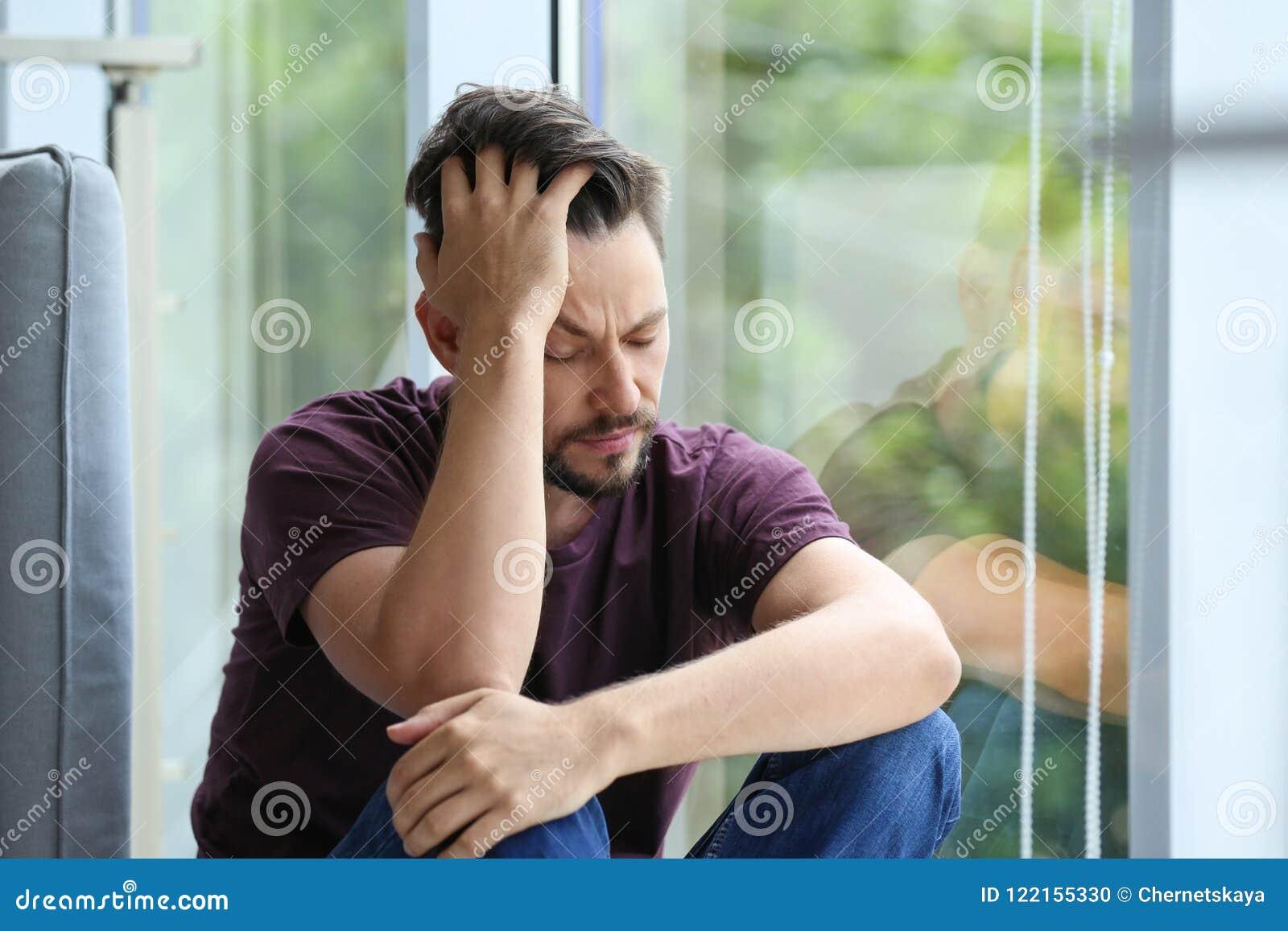 Homem deprimido só perto da janela